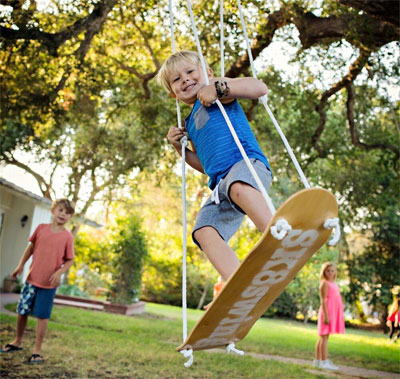 Boy on Skateboard Swing Hanging from tree